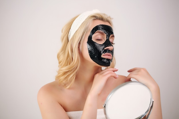 Meisje draagt een zwart masker op haar gezicht zorgzaam in de spiegel kijken