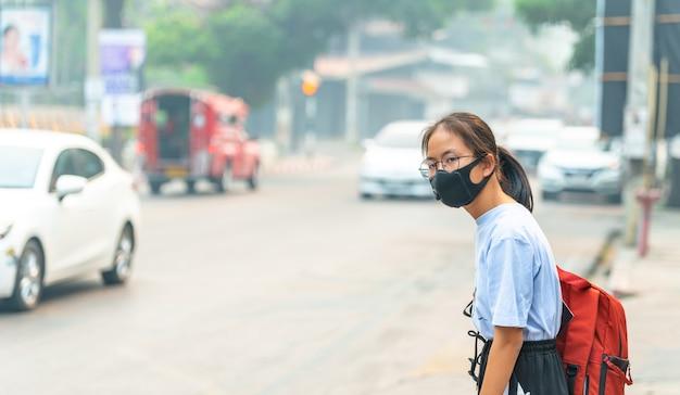 Meisje draagt een zwarte neuzen n95 doek om stof pm 2.5 te voorkomen dat een zeer hoge waarde heeft in een stad met verkeer