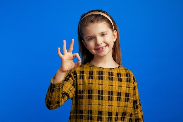 Meisje draagt geruite jurk die naar de camera kijkt en een goed teken toont
