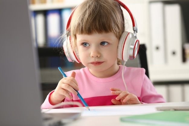 Meisje draagt hoofdtelefoon gebruik mobiele computer