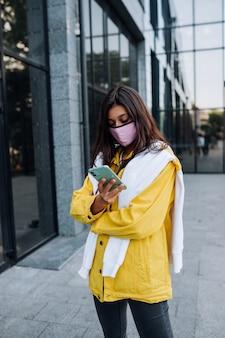 Meisje draagt masker poseren op straat. mode tijdens de uitbraak van het coronavirus.