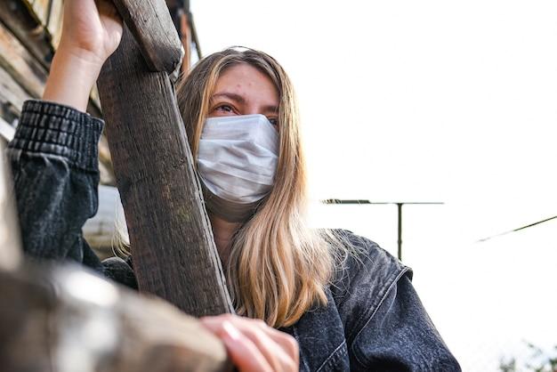 Meisje draagt medisch masker vanwege luchtvervuiling of virusepidemie in de stad. vrouw met medisch en gezichtsmasker op een blauwe hemel.