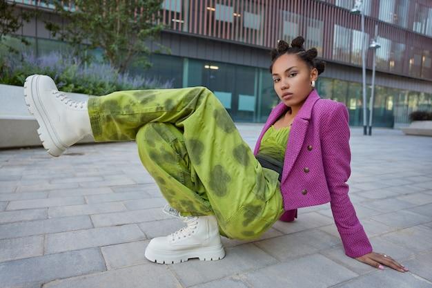 Meisje draagt modieuze kleding en witte laarzen heeft lichte make-up poses tegen stedelijke gebouwen poses om fotopraktijken te maken breakdance ziet er serieus uit