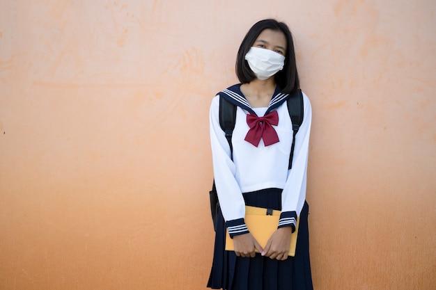 Meisje draagt uniform en masker houdt boek vast