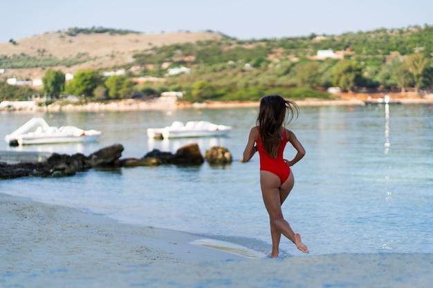 Meisje draait op strand. atletische gelukkige vrouw die in trendy sexy rode bodysuit aanstoot die van zon het uitoefenen geniet. gezonde levensstijl. leuke wandeling langs de kust. perfecte fitness lichaamsvormen.