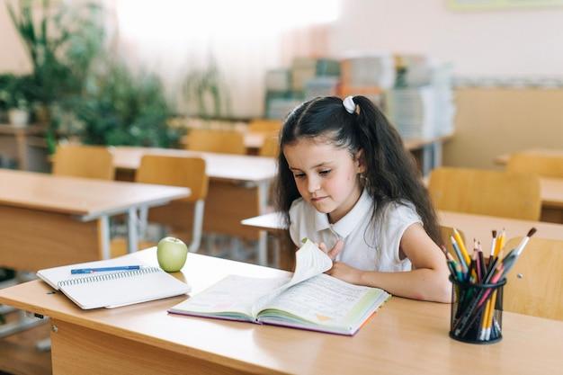 Meisje draait pagina in de klas