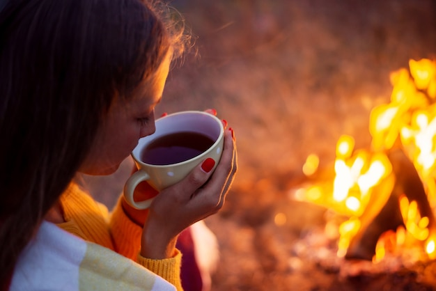 Meisje drinken warme thee zitten in de buurt van helder vreugdevuur. vakantie in de natuur, rusten en ontspannen buiten in de herfst.