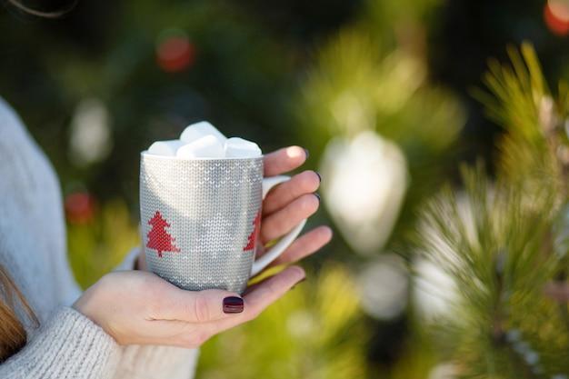 Meisje drinkt een warme drank met marshmallows in de winter in het bos. een gezellige winterwandeling door het bos met een warm drankje. close-up die een mok houdt