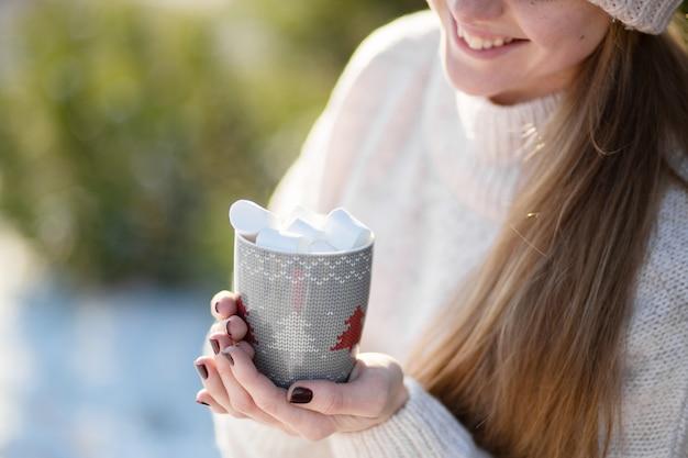 Meisje drinkt een warme drank met marshmallows in de winter in het bos, een gezellige winterwandeling door het bos met een warme drank, close-up met een mok