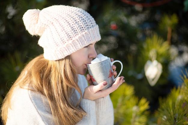 Meisje drinkt een warme drank met marshmallows in de winter in het bos. gezellige winterwandeling door het bos met een warm drankje