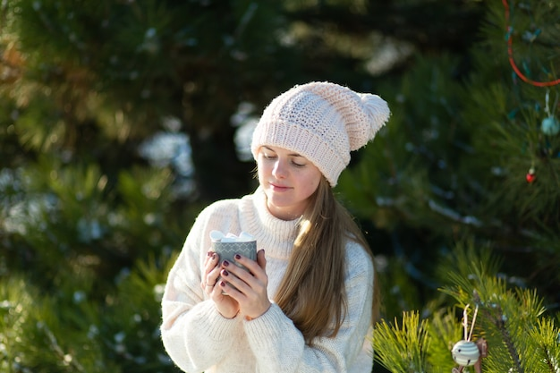 Meisje drinkt een warme drank met marshmallows in de winter in het bos.