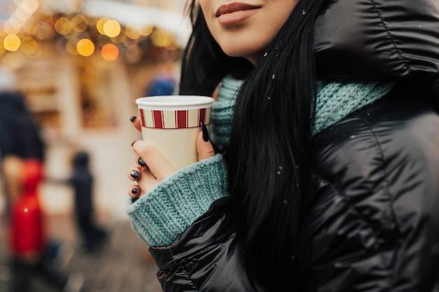 Meisje drinkt een warme drank op de kerstmarkt