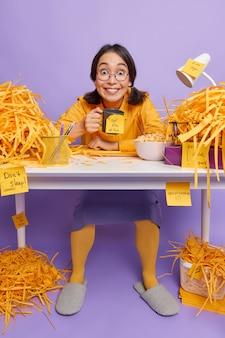 Meisje drinkt koffie maakt aantekeningen op stickers om te onthouden wat ze moet doen zit aan bureau op paars draagt ronde bril vrijetijdskleding doet huiswerk werkt in kast