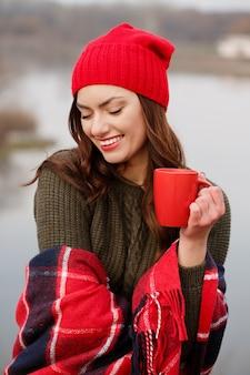 Meisje drinkt koffie uit een rode kop