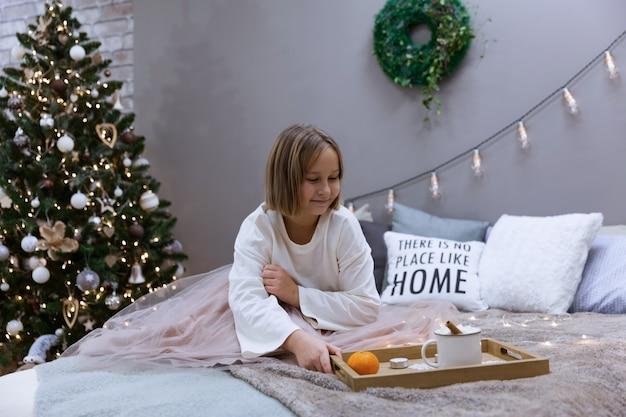 Meisje drinkt thee en eet op bed in de slaapkamer te midden van een feestelijke kerstboom, soft focus