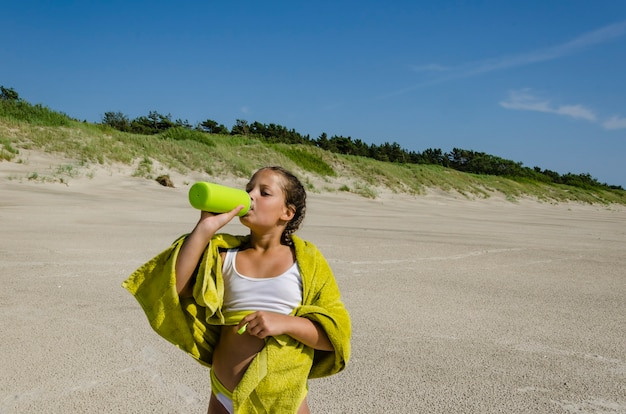 Meisje drinkt water aan de kust