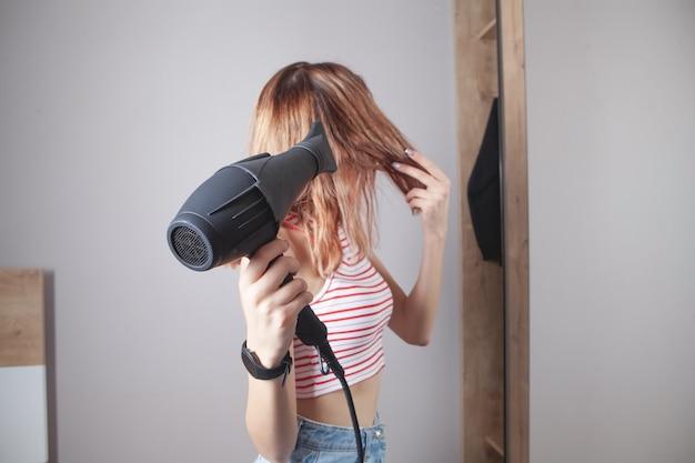 Meisje droogrek met haardroger in huis.
