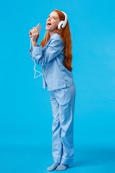 Meisje droomt ster te worden. verticale full-length portret charmante en zorgeloze roodharige tiener in nachtkleding, download karaoke-app, luisteren muziek in koptelefoon, zingen in telefoon