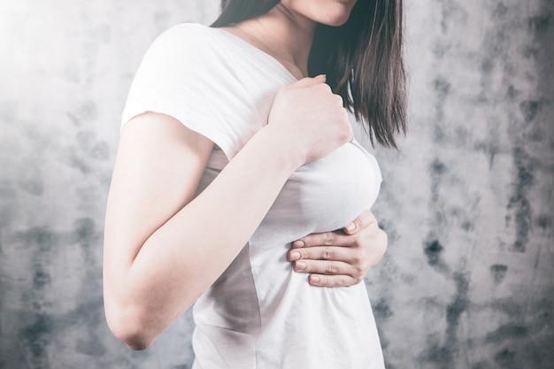 Meisje drukt haar handen op haar pijn op de borst