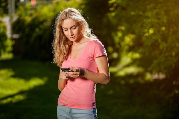 Meisje een bericht aan het typen aan de telefoon in het park