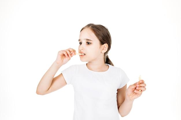 Meisje eet gebakken aardappelen, frietjes, wit t-shirt, isolaat, studio, tiener, fastfood