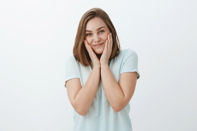 Meisje eindelijk ontdoen van acne met nieuw gezichtsmasker. charmante tevreden en heldere vrouw aanraken van wangen en glimlachend vreugdevol gevoel mooi en fris huidproblemen op te lossen die zich voordeed tegen grijze muur