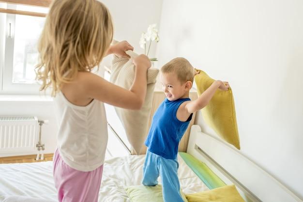 Meisje en een jongen die en een kussengevecht op een bed glimlachen hebben
