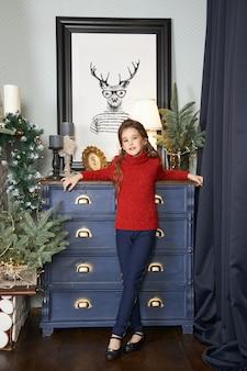 Meisje en een kerstochtend, een kind dat tegen de binnenkant van de kerstboom poseert