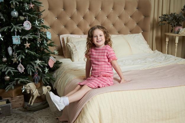 Meisje en een kerstochtend, een kind poseren tegen de achtergrond van de kerstboom interieur