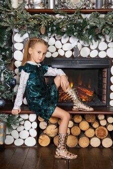Meisje en een kerstochtend, een kind poseren tegen de muur van de kerstboom interieur