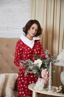 Meisje en een kerstochtend, een kind poserend tegen het interieur van de kerstboom