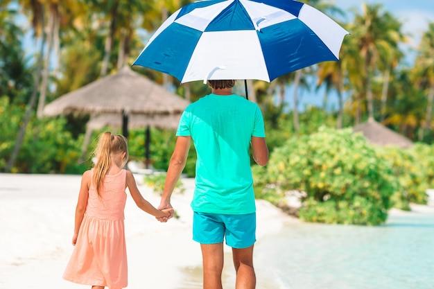 Meisje en gelukkige papa die op het strand met een paraplu lopen