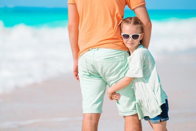 Meisje en gelukkige papa die pret hebben tijdens strandvakantie