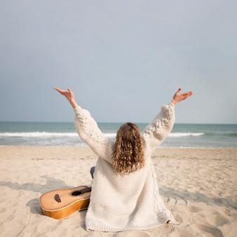Meisje en gitaar op het strand van het achter schot
