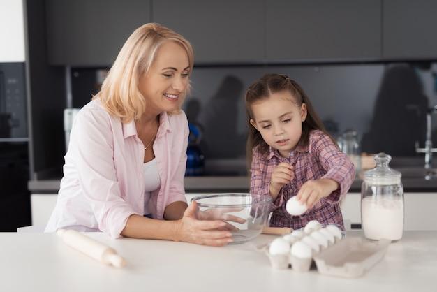 Meisje en haar grootmoeder in keuken en het voorbereiden van gebakjes.