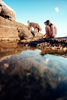 Meisje en haar hond die rotsachtig strand onderzoeken