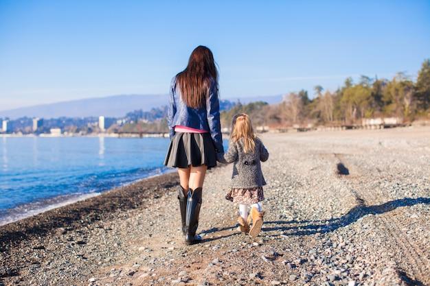 Meisje en haar moeder die op het strand in de winter zonnige dag lopen