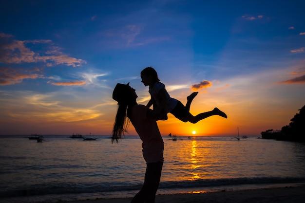 Meisje en haar moeder die pret hebben bij zonsondergang op het eiland boracay, filippijnen