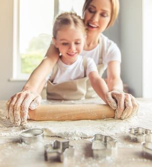 Meisje en haar mooie moeder in schorten glimlachen.