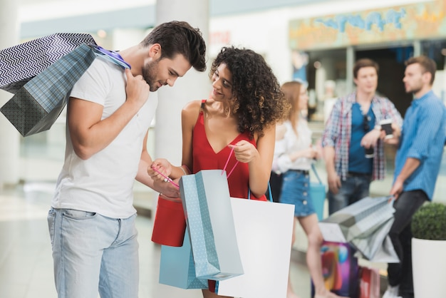 Meisje en haar vriend winkelen in het winkelcentrum.