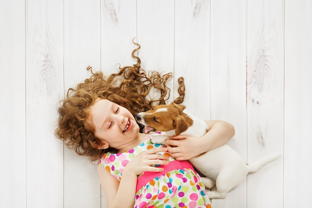 Meisje en haar vriendenpuppy die op houten vloerachtergrond spelen.