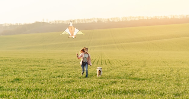 Meisje en hond spelen met kite