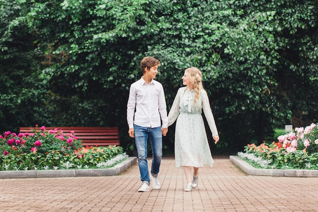 Meisje en jonge man zittend op een bankje, eerste date, communicatie kus, kennismaking