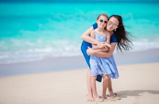Meisje en jonge moeder tijdens strandvakantie