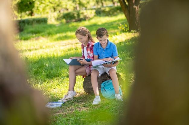 Meisje en jongen betrokken bij lezen in park