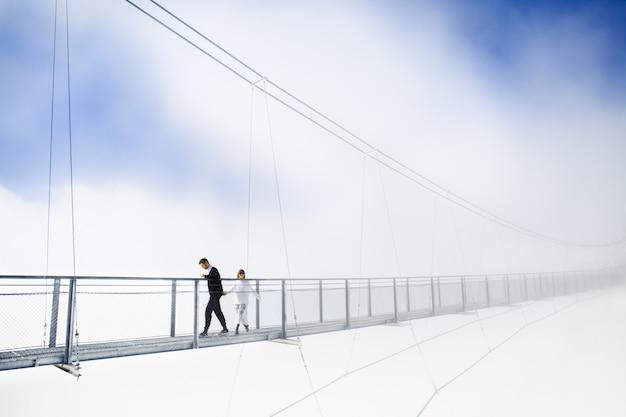 Meisje en jongen die op brug in wolken lopen