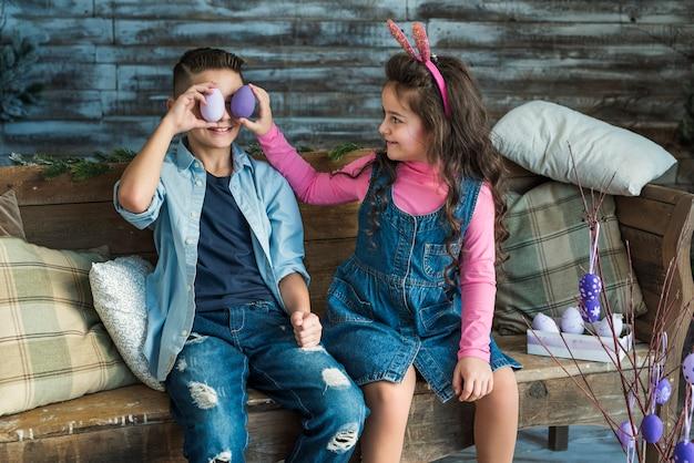Meisje en jongen die paaseieren houden bij ogen
