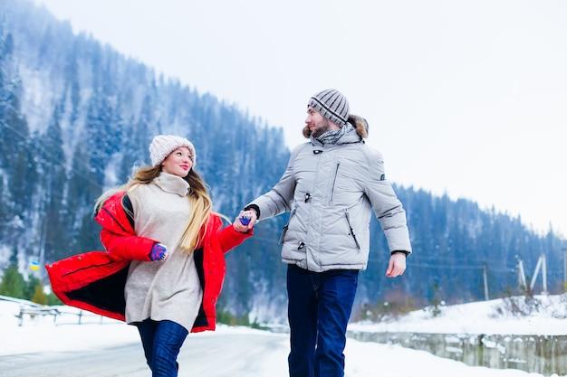 Meisje en jongen houden elkaars hand vast en rennen langs de weg in de winterbergen
