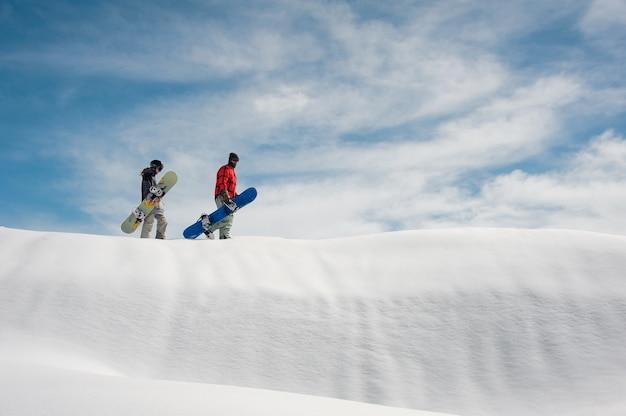 Meisje en jongen in ski-uitrusting met snowboards lopen op een besneeuwde weg
