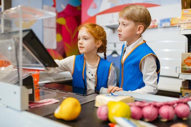 Meisje en jongen in uniform bij de kassa spelen verkoopster